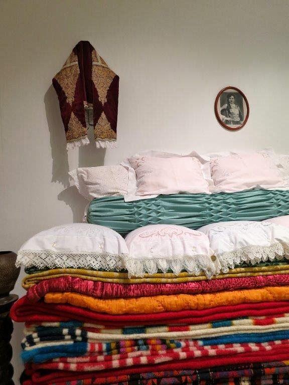 LA PASIÓN GRIEGA .: NOVIAS: TRADICIÓN Y MODA EN GRECIA - En la exposición se exhibe el γιούκος/yiukos, que es la dote tradicional de la ciudad de Mégara: coloridas colchas, almohadas, cojines, cubertores, sábanas cuidadosamente dobladas… todas las prendas colocadas la una sobre la otra, ya que la altura que alcanzaba la dote era el indicador del estatus económico de la familia de la novia.
