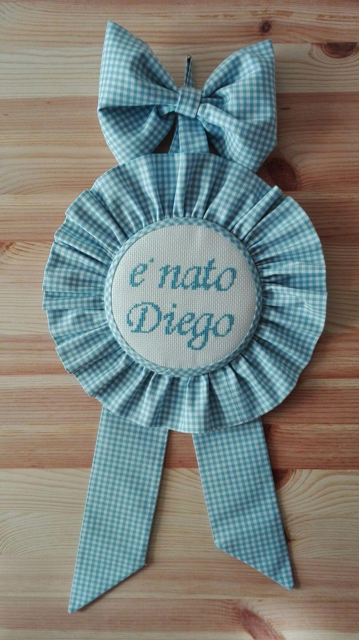 Fiocco nascita Diego, realizzato con passione, realizzato interamente a mano, con ricamo a punto croce, in tessuto in puro cotone a quadretti vichy. È possibile realizzarne versioni personalizzate, su ordinazione.