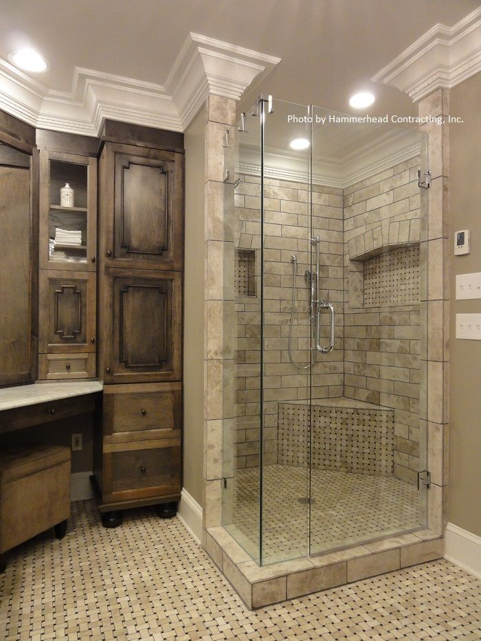 Click on the image to find out the cost of a bathroom remodel in your area. Incorporate medium stained wood cabinetry, can lights, glass shower wall and triple stacked crown molding in your remodeling project.