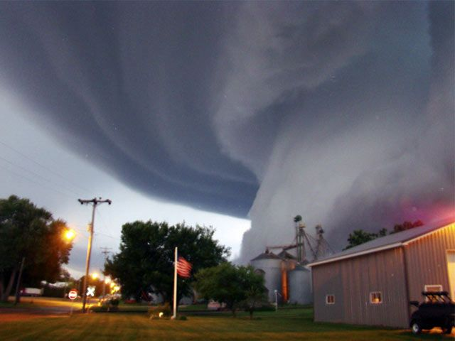 A huge tornado funnel cloud touches down in Orchard, Iowa, 10 June 2008 at 9:04pm.  The Globe Gazette and Mitchell County Press News reported that Lori Mehmen of Orchard, took the photo from outside her front door.  Mehmen said the funnel cloud came near the ground and then went back up into the clouds.  Besides tree and crop damage, no human injuries were reported. (AP Photo/Lori Mehmen)