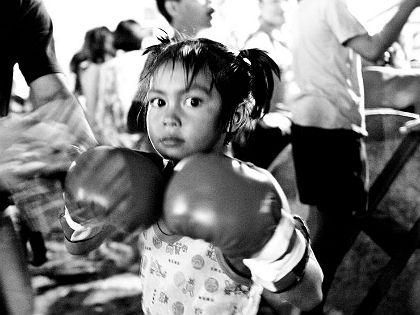 Gyerekharcosok klubja Sandra Hoyn fotóriporter Thaiföldön nyaralt, amikor Bangkokban egy thai boksz összecsapás nézőterén találta magát, ahol a résztvevők zöme alig lehetett több 6 évesnél. A fotós négy hetet töltött a gyerekekkel, elkísérte őket az edzésekre, a versenyekre és otthonukba. Gyerekharcosok című fotósorozatát róluk készítette.