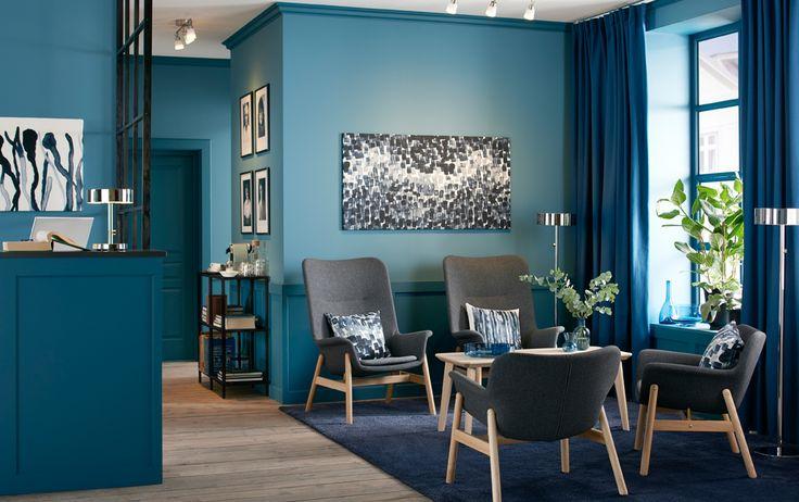 Váró, négy sötétszürke fotellel egy kék irodai recepción.