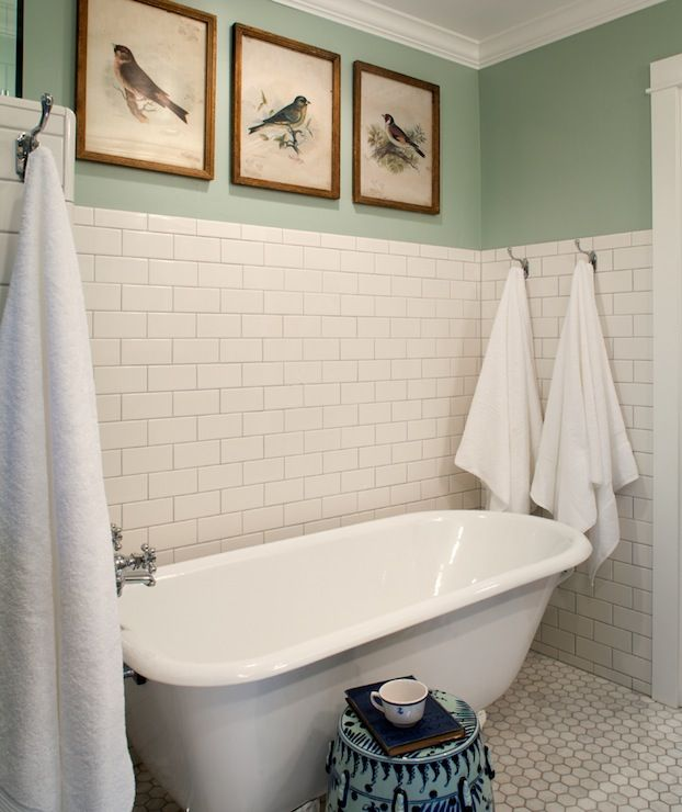source: Rustic Rooster Interiors      Beautiful bathroom with partially tiled white subway tile wall and marble hexagonal floor tile. A white claw foot tub stands in the tiled nook beside a blue and white garden stool. Handy towel hooks hold fluffy towels within arms reach of the tub. The sage green walls are adored with framed vintage bird prints.