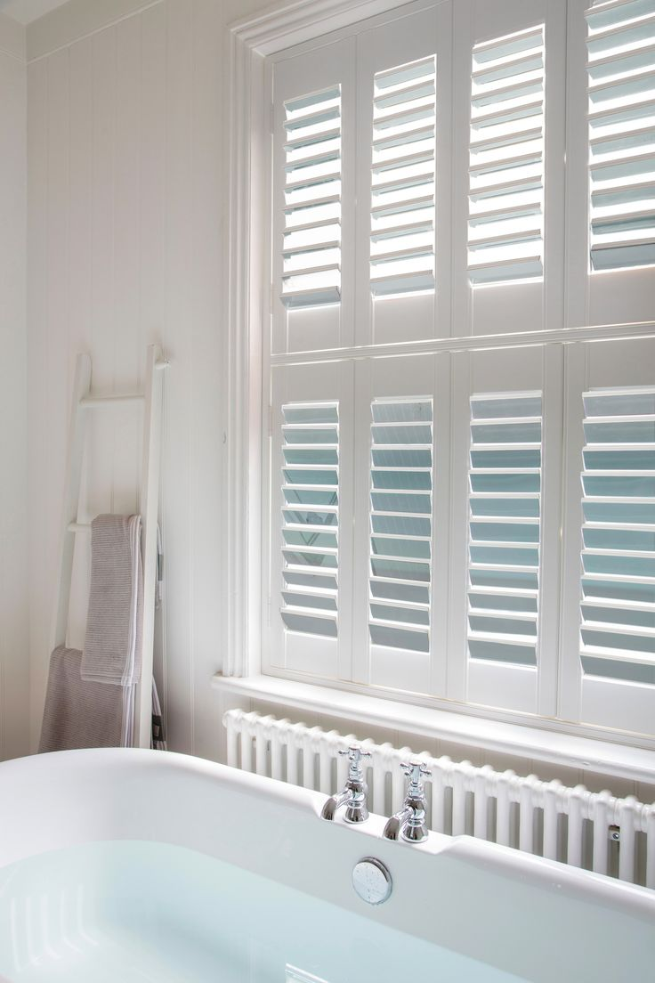 Luxaflex® Silver Mirror Shutters reflect the cool blue of water beautifully in this calm and serine bathroom. #Luxaflex #InteriorShutters #MirroredInteriors #HomeStyle #Bathroom
