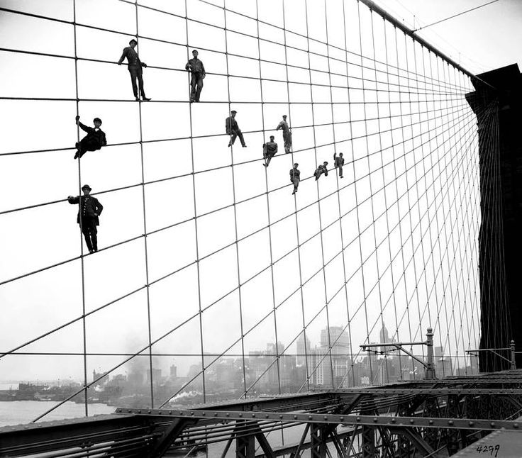 In this Oct. 7, 1914 photo provided by the New York City Municipal Archives, painters are suspended from wires on the Brooklyn Bridge in New York. Over 870,000 photos from an archive that exceeds 2.2 million images have been scanned and made available online, for the first time giving a global audience a view of a rich collection that documents life in New York City. (AP Photo/New York City Municipal Archives, Department of Bridges/Plant & Structures, Eugene de Salignac) MANDATORY CREDIT/...