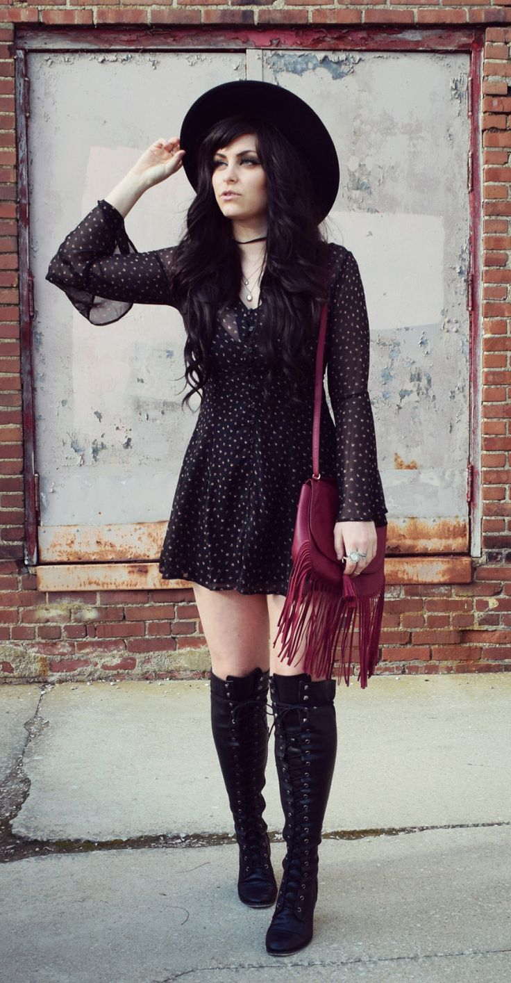 White polka dotted black long sleeved dress, knee-high laced boots in black, black hat, a choker, and a maroon tasseled handbag