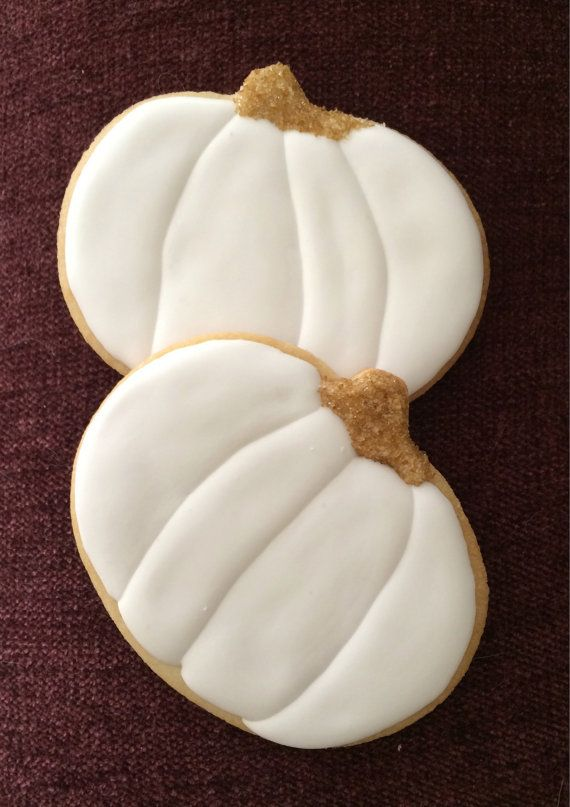 pumpkin sugar cookies decorated with white royal icing and gold sanding sugar