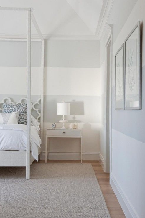 Exquisite bedroom features white and gray striped walls framing a white canopy bed with quatrefoil headboard, Ironies Asilah Bed, next to a sleek white nightstand.