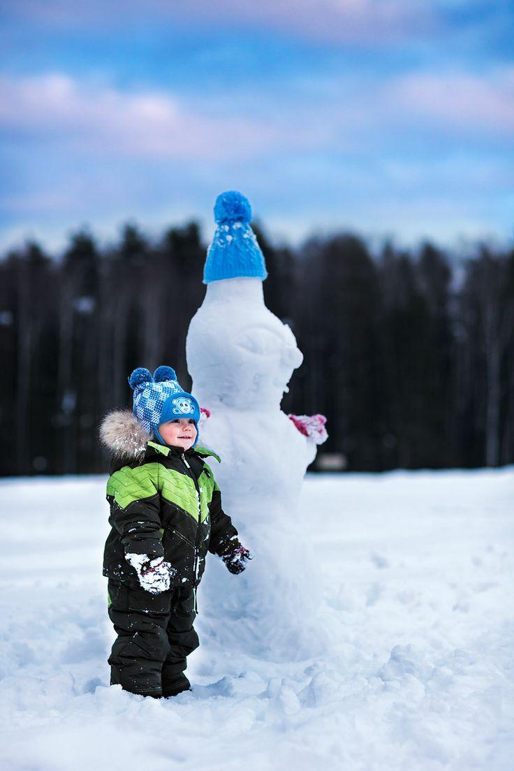 boy in a blue cap next to a snowman in a blue cap
