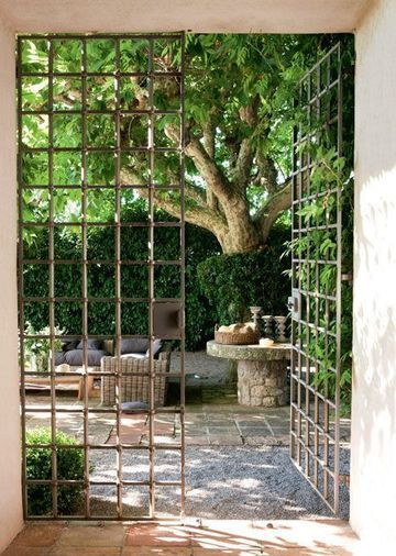 Awesome gates create a sense of mystery. Love the stone table, too.