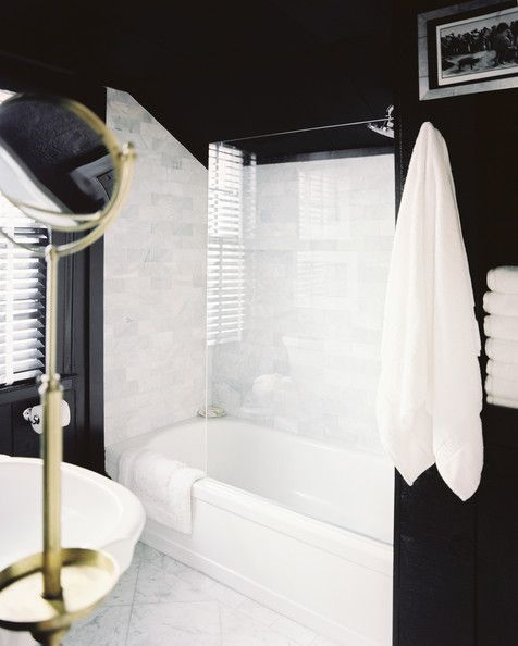 November 2012 Issue Photo - A black bathroom with marble tile and a brass mirror