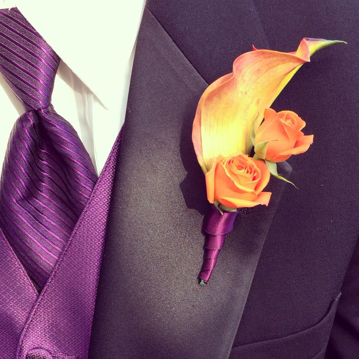 The groomsmen in their eggplant ties and vests with plum and orange boutonnière.