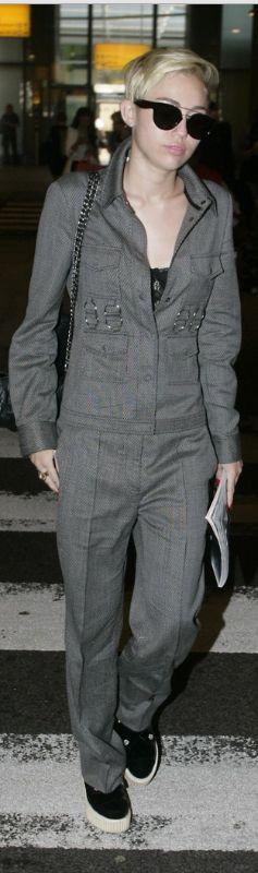 Who made  Miley Cyrus' gray jumpsuit, black handbag, and black sunglasses?