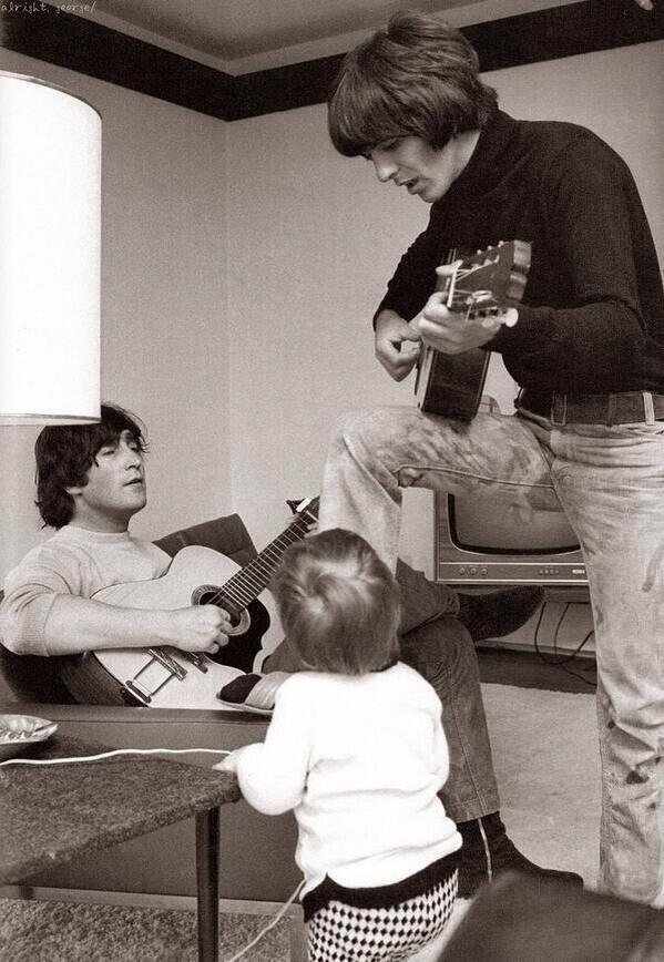 John Lennon y George Harrison en casa tocando la guitarra, mientras el hijo de John (Julian Lennon) los observa