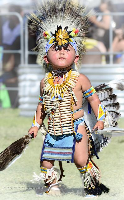 Young Native American dancer in full dress. The feathered head dress looks as though it's about to slip down over those big brown eyes.