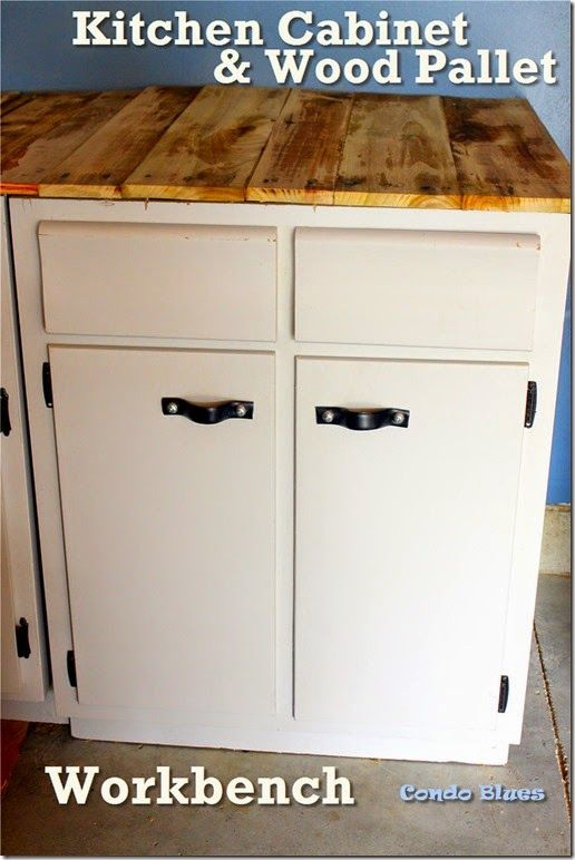 She recycled kitchen base cabinets into a workbench with leather belt door pulls, and made the top out of a wood pallet. Lots of tool storage!