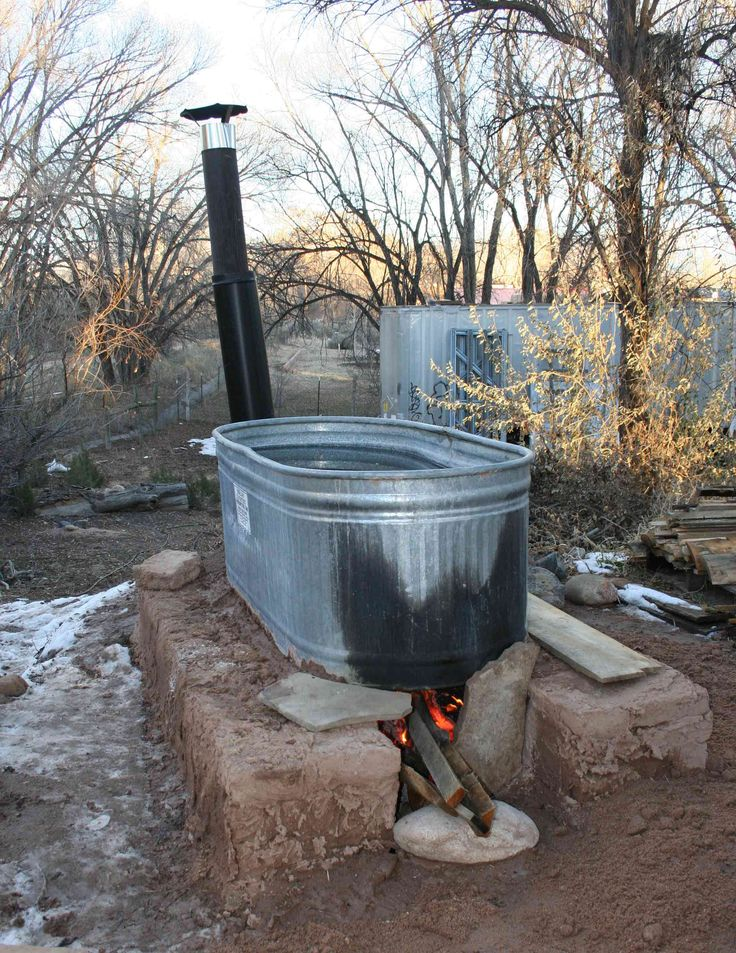 wood fired stock tank hot tub on 1/4 size adobe block base with smoke stack.  Adobes made in house with a nine-block frame that looks sort of like a ladder. Pojoaque, New Mexico, USA. 2013