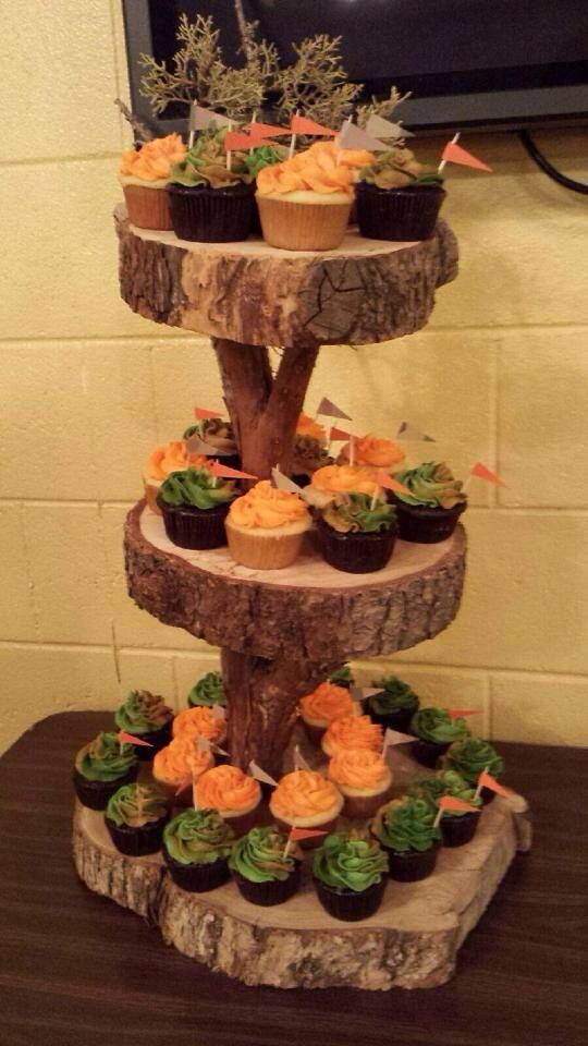 Camo and orange frosted cupcakes on a custom three tier log cake stand for a hunting themed baby shower / party