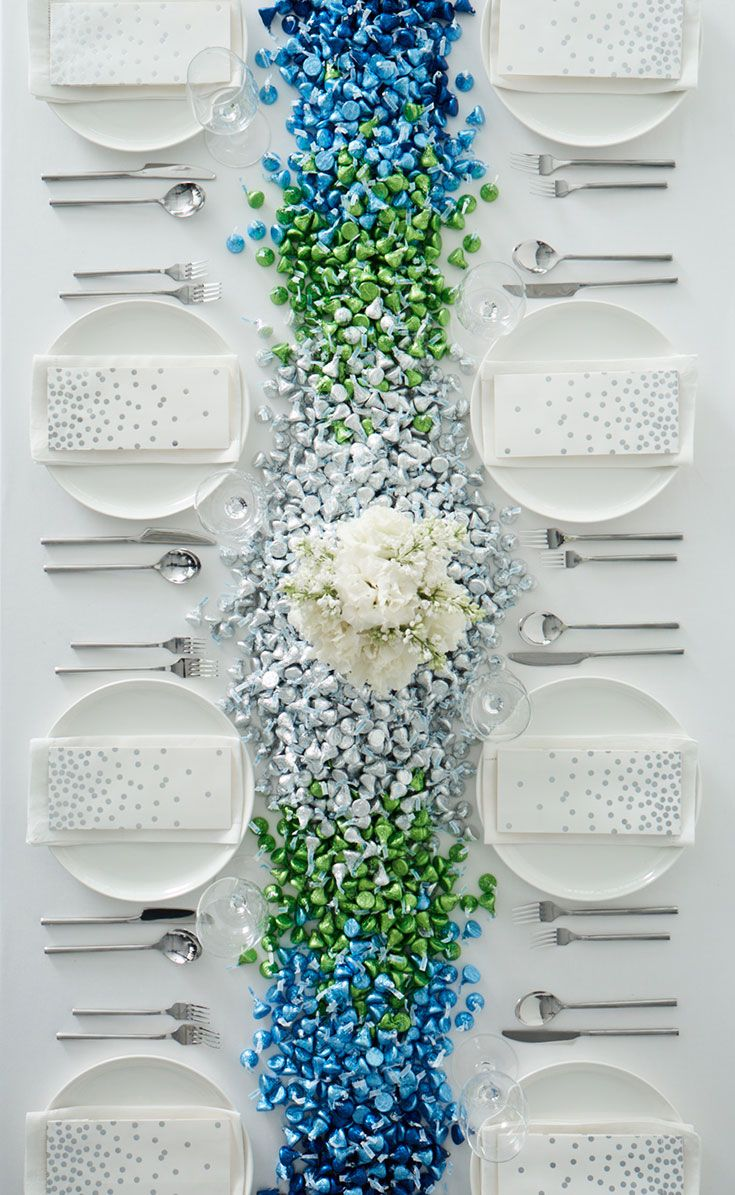 An Ombre Centerpiece Made with KISSES Milk Chocolates | Martha Stewart Weddings -  This artful arrangement, perfect for a wedding reception or engagement party, is what tasteful décor is all about. We chose KISSES Milk Chocolates wrapped in two different shades of blue and light green, as well as silver, a neutral that helps balance the look. You won't have to purchase party favors since your guests will be more than happy to take handfuls of their table's centerpiece home!
