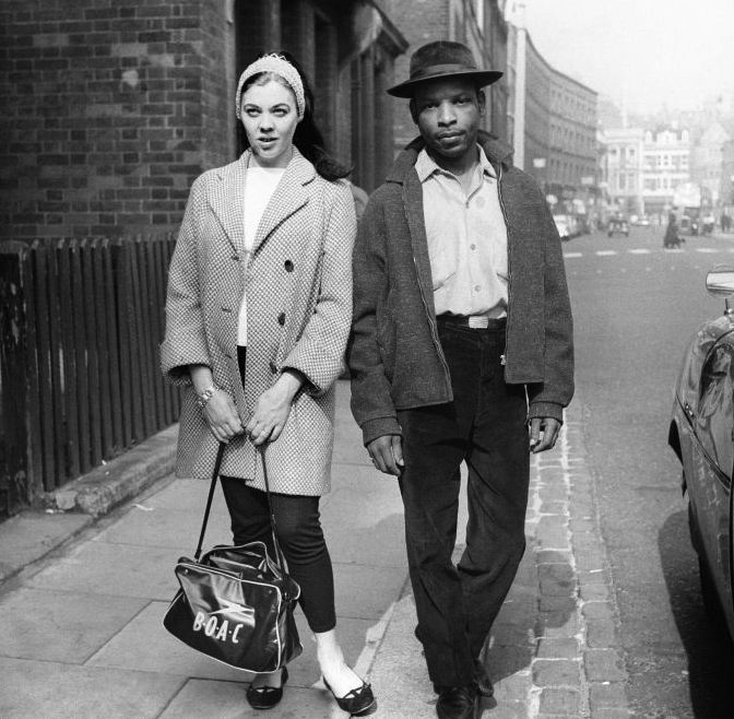 1958: A West Indian man and his white girlfiend walk through Notting Hill Gate after the race riots