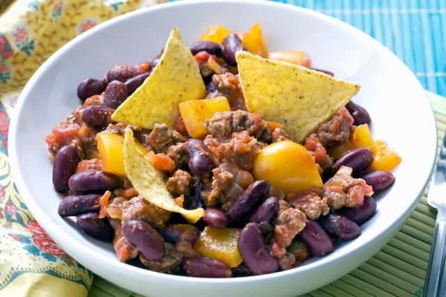 This is an easy layered slow cooker meal, made with a flavorful taco-seasoned ground beef mixture, tortilla chips, cheese, corn, and chili.