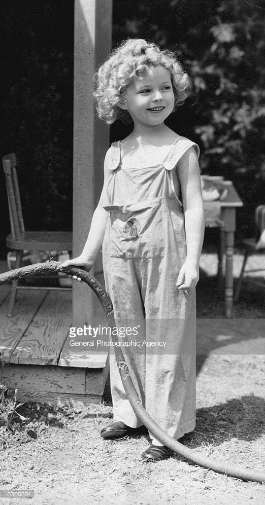 1935: Shirley Temple (1928 - ) the American child star started performing in films at three years. She entered politics in the 60's and took on several ambassador positions representing her country. Pictured with the garden hose and an impish grin on her face.