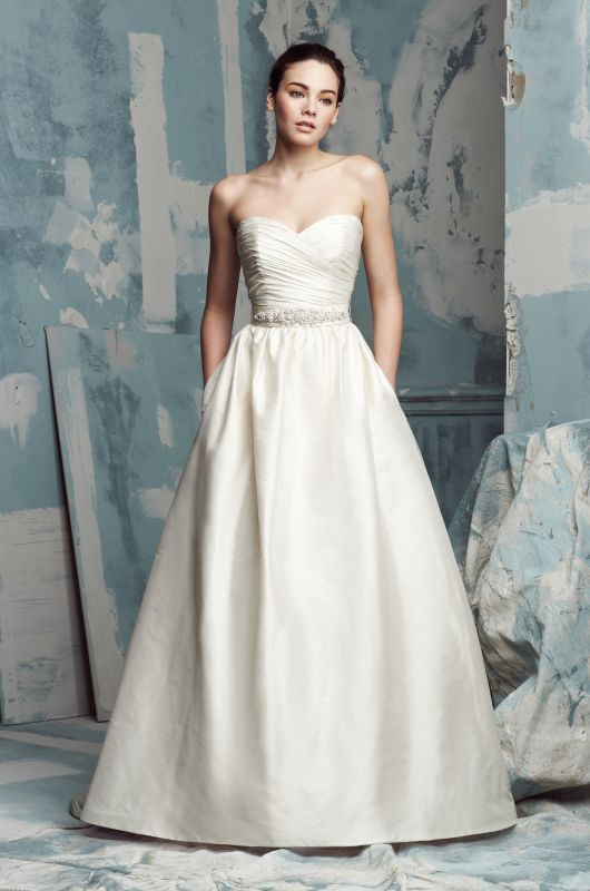 @palomablancawed Silk Dupioni Wedding Dress. Strapless crossover ruched bodice with a removable beaded tie up band at waist. Full gathered skirt with side #pockets. Chapel Train. Style 4104 #PalomaBlanca #PalomaGowns Paloma Blanca Wedding Gown