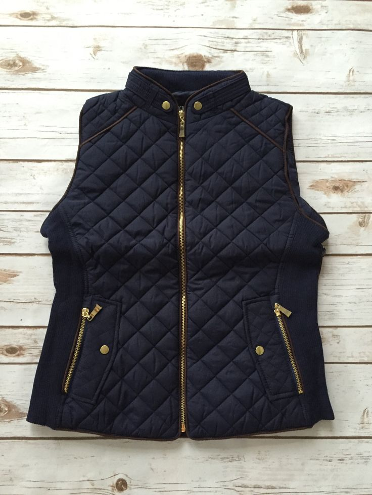This is the perfect vest for fall. Our quilted navy vest has faux suede pipping and gold zipper detail. 100% polyester.