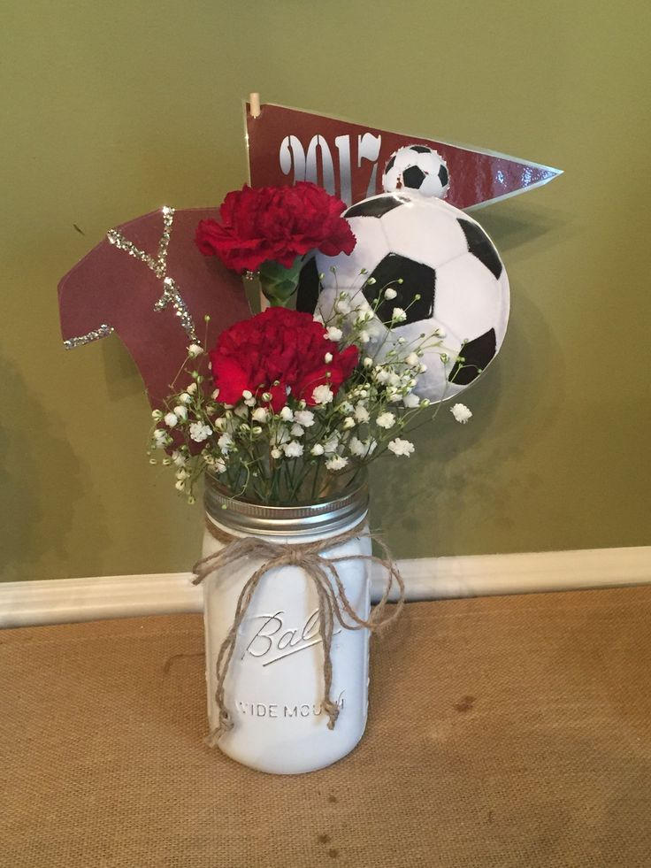 Soccer banquet centerpiece using burgundy carnations, baby's breath, rice to stabilize flowers
