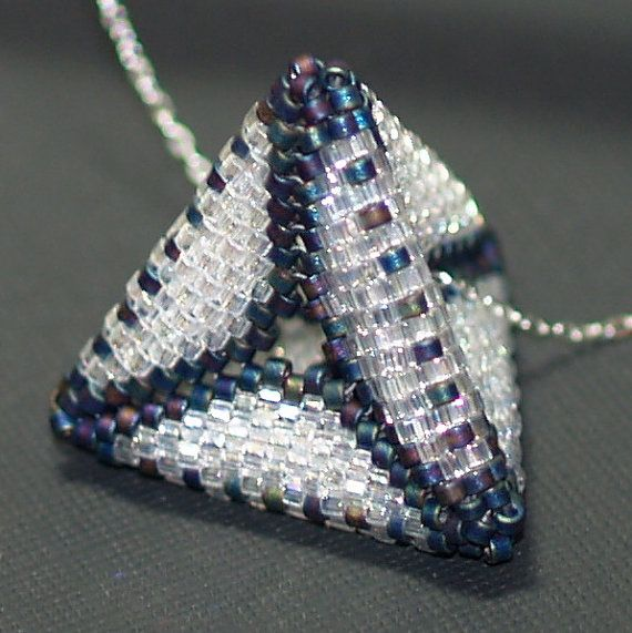 Constructed of four peyote triangles, woven together to create a pyramid shape, There's a space in the center for the sterling silver chain to slip through.