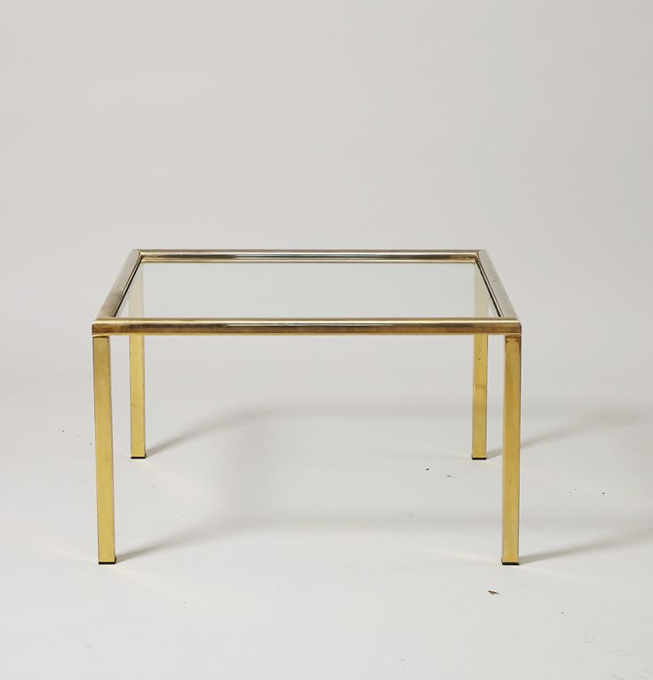 Circa 1960  Elegant side table table in mint condition that a solid brass frame in vintage mint condition and high-quality glass top. In excellent original state with no signs of visible wear.  SIZE  Height: 45 cm  Width: 76 cm  STOCK  1 Available