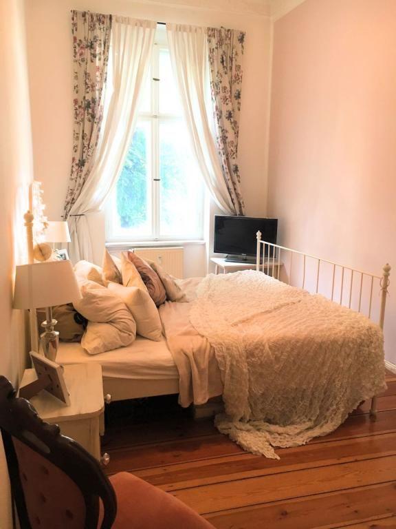 Gemütliche Einrichtungsidee: Bett mit vielen Decken und Kissen, geblumte Vorhänge, Lichterkette – perfekt für verregnete Herbsttage. #Einrichtung #WGZimmer