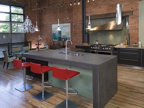 I love concrete benchtops. I especially love this one in steel grey set off by those fab red bar stools!