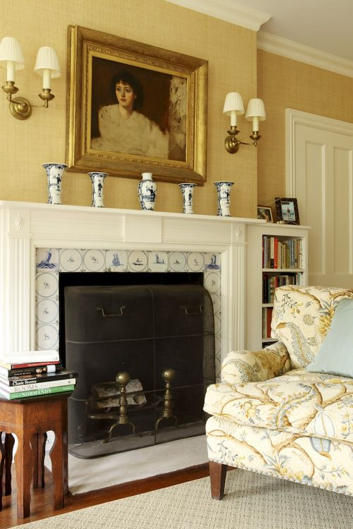 The Master Bedroom fireplace is surrounded by antique Delft tiles and the garniture is English Worcester in the Dutch taste. The painting, an unfinished sketch, is British from the early 20th century. The chair is covered in a print from Brunschwig & Fils ~ via Thomas Jayne