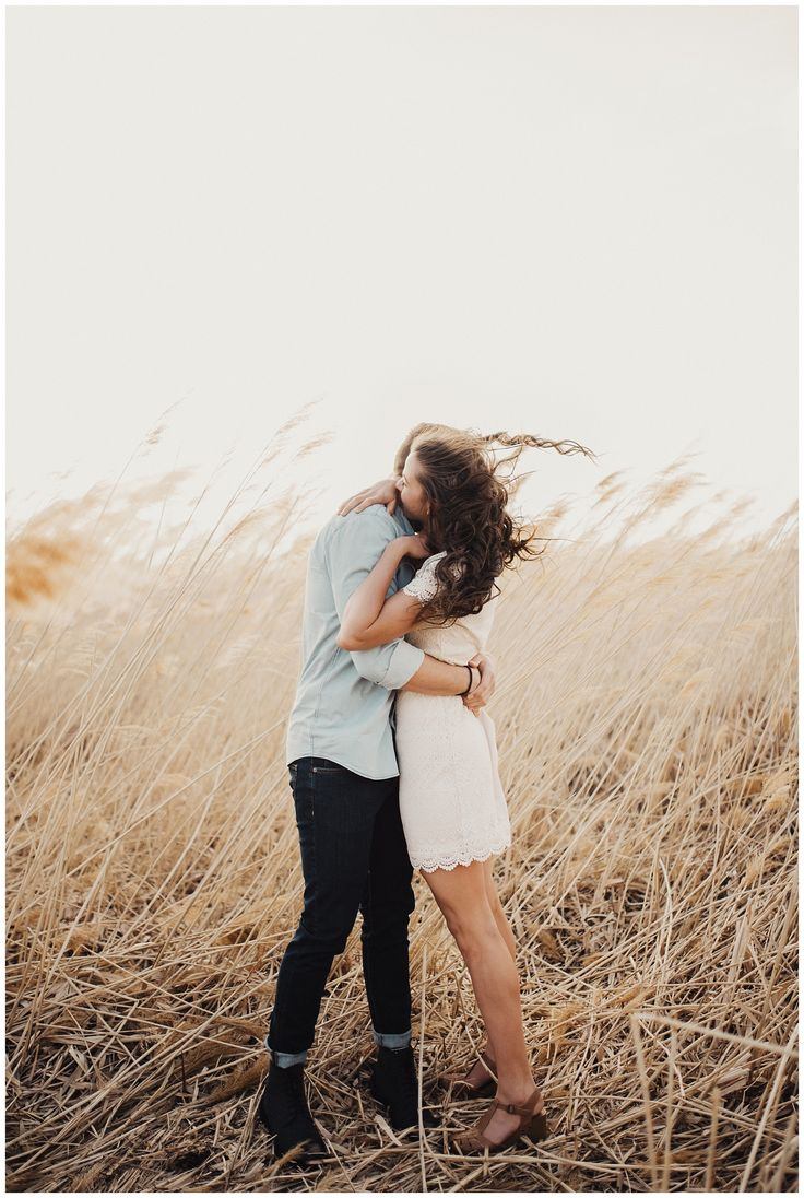 windy engagement photography session in a wheat field