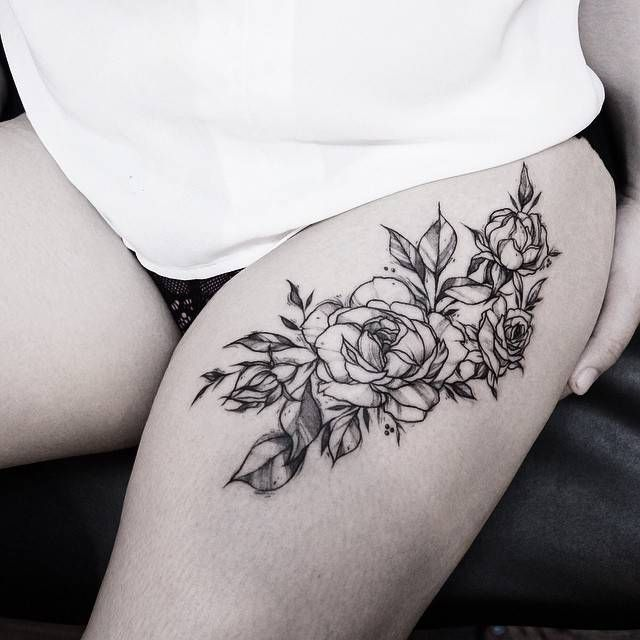 Thigh tattoo of a bunch of roses.