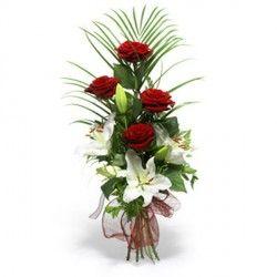 Un elegante fascio di fiori misti funebre con rose rosse, lilium e foglie di palma. Una composizione semplice per esprimere il vostro cordoglio.