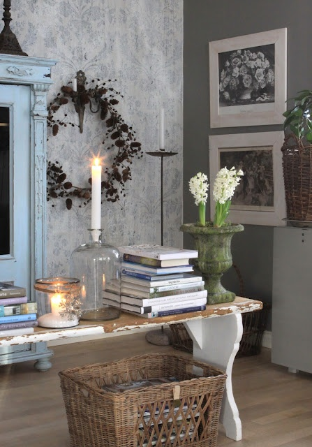 Blonde wood floor, contrasting grey walls and white picture frames and furniture, wicker basket, forced bulbs and candles - stunning
