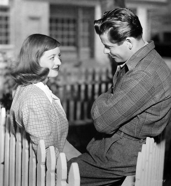 """Bette Davis and Glenn Ford chat on the set of """"A Stolen Life"""""""