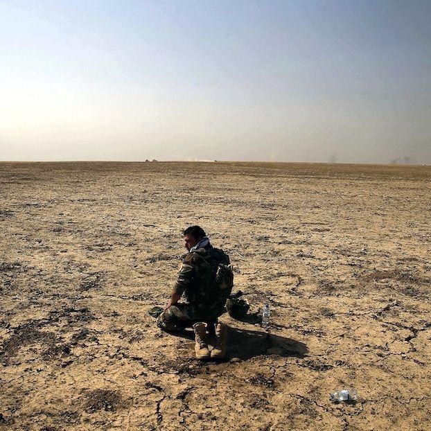 Un soldato dei peshmerga curdi (l'esercito del Kurdistan iracheno) prega a poca distanza da Mosul