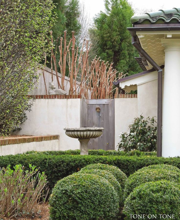 brick coping on stucco; wood gate wood fence above brick-coped white wall in courtyard beyond