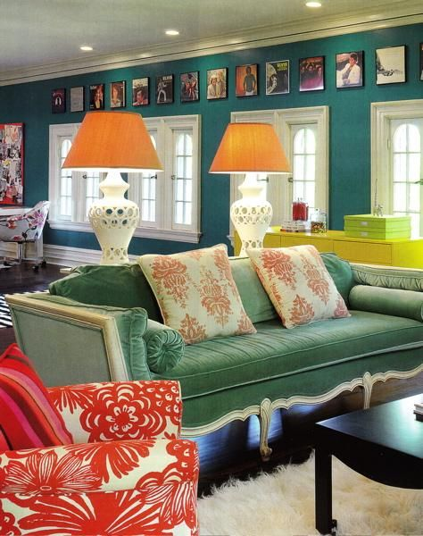 Beaux Arts Mansion in St. Louis Turquoise paint wall color. French windows, white lamps with orange shades, green velvet French sofa, salmon pink cream throw pillows, red flower print chair, Jonathan Adler black coffee table, cream flokati rug and bright yellow ebay dresser chest. turquoise celadon green salmon pink, cream black brown family room den colors.