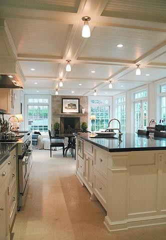 This shows all of the elelments that I would llike -- coffered ceiling, white cabinets, dark counters, white floor, fireplace seating area, but with seatboxes under the windrows and the TV over the fireplace.
