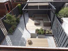 Onze kleine achtertuin met grijze schutting, betegeld met 60x60 tegels in chinees hardsteen en voorzien van een eiken houten terras met heerlijke loungebank en een pergola met schaduwdoek.