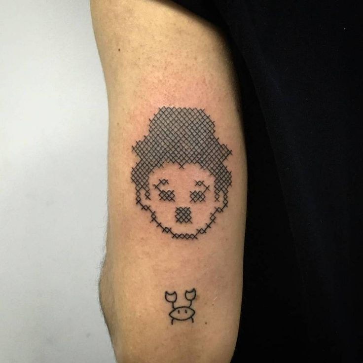 Hand poked cross-stitch Charlie Chaplin tattoo on the back of the left arm.