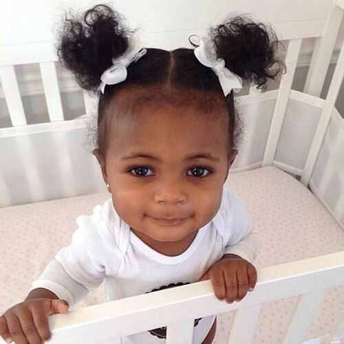 Baby in crib with curly pig tails