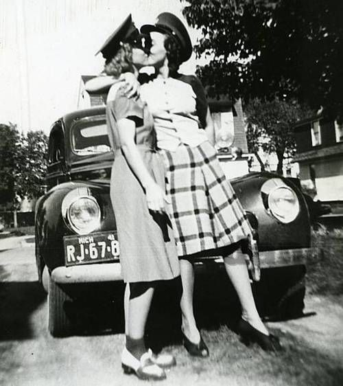See an image of two women kissing. I'm surprised that these women engaged in a public kiss. At this time in history, it was incredibly dangerous for same-sex couples to be affectionate.