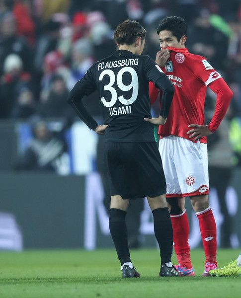 Yoshinori Muto of Mainz chats with Takashi Usami of Augsburg during the Bundesliga match between 1. FSV Mainz 05 and FC Augsburg at Opel Arena on February 10, 2017 in Mainz, Germany.