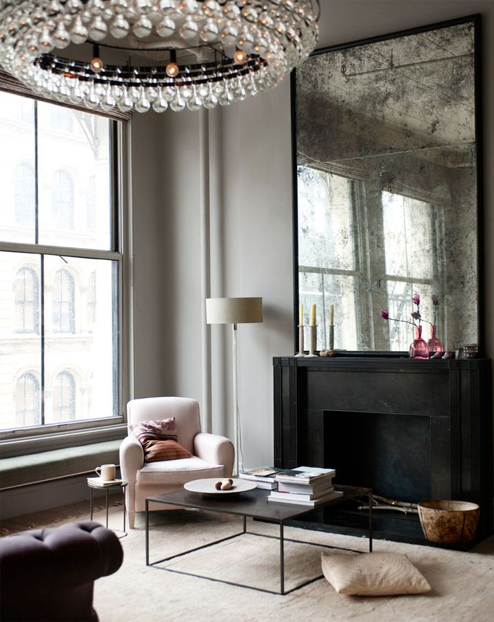 Loft In New York. Black fireplace, scale of antiqued mirror, tear drop chandelier, light area rug.