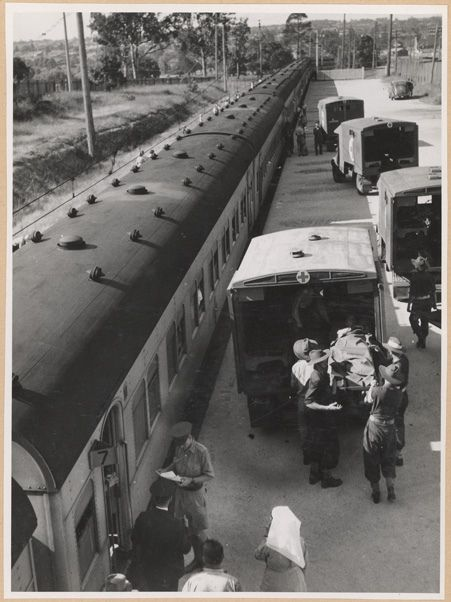 Title: Ambulance train at Rosehill transferring wounded into ambulance, Rosehill, NSW Dated: 07/02/1944